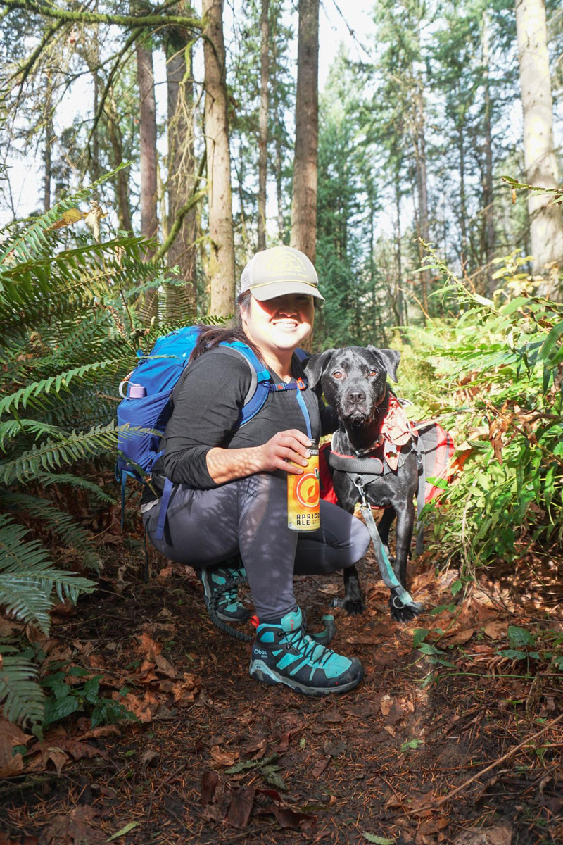 Doris Wang and her black labrador pose for a photo with a Pyramid apricot ale on a forest trail, surrounded by pine trees and ferns