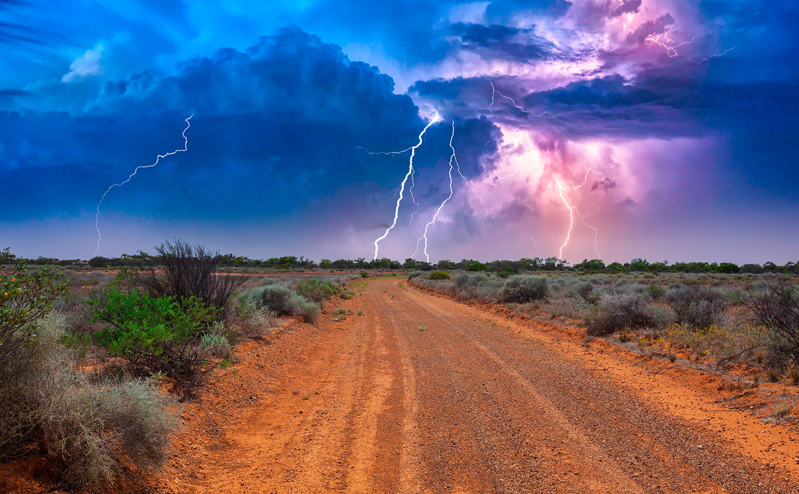 red sand of australian outback with lightning in the sky
