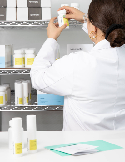 An Apostrophe pharmacy technician checking the label on a white pill bottle in front of a metal shelf containing various prescriptions for Latisse and acne treaments.