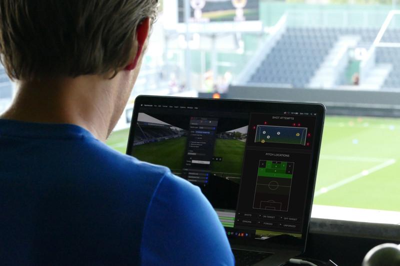 モニターでシュートと選手のポジションを分析する男性