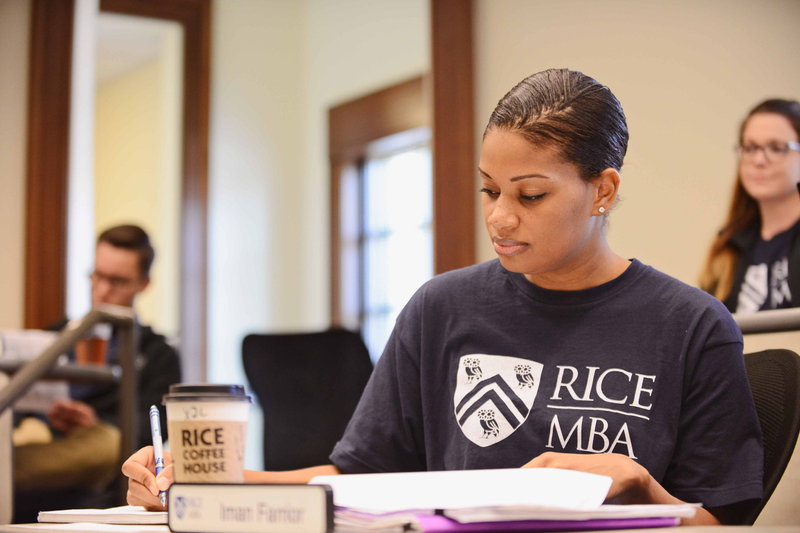 Rice University MBA student taking notes in class with a Rice coffee sleeve on her cup