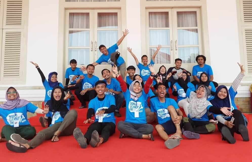 A group of young Indonesians wearing World Cleanup Day shirts with their arms up in the air and smiles sitting on stairs covered with a red carpet.