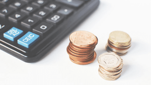 Piles of coins next to a calculator on a desk #startup
