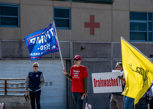 a red cross is seen on a wall in the background, in the foreground a mask-less trump supporter wearing a red trump 2020 shirt, and red hat holds up a trump 2020 flag with one hand, and is wearing dark sunglasses to the right of that person is a white sign with red text that reads 'Brainwashed!' and the the right of that sign is a don't tread on me flag