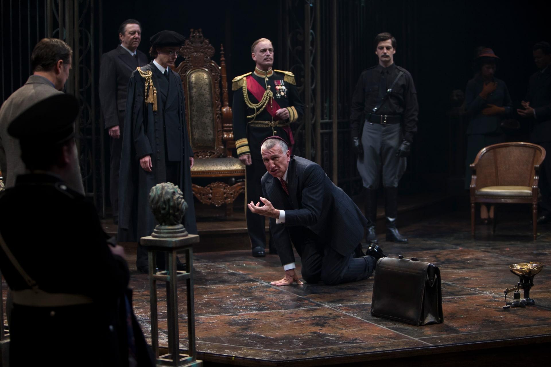 Distraught man in suit and yarmulke kneels pleading before standing figures on brown marbled stage.
