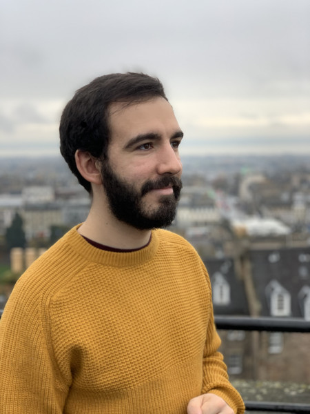 Jacob standing in the foreground in an orange jumper, with a city landscape behind him.