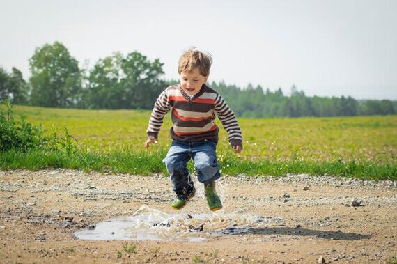 Foto de menino pulando em uma poça de água