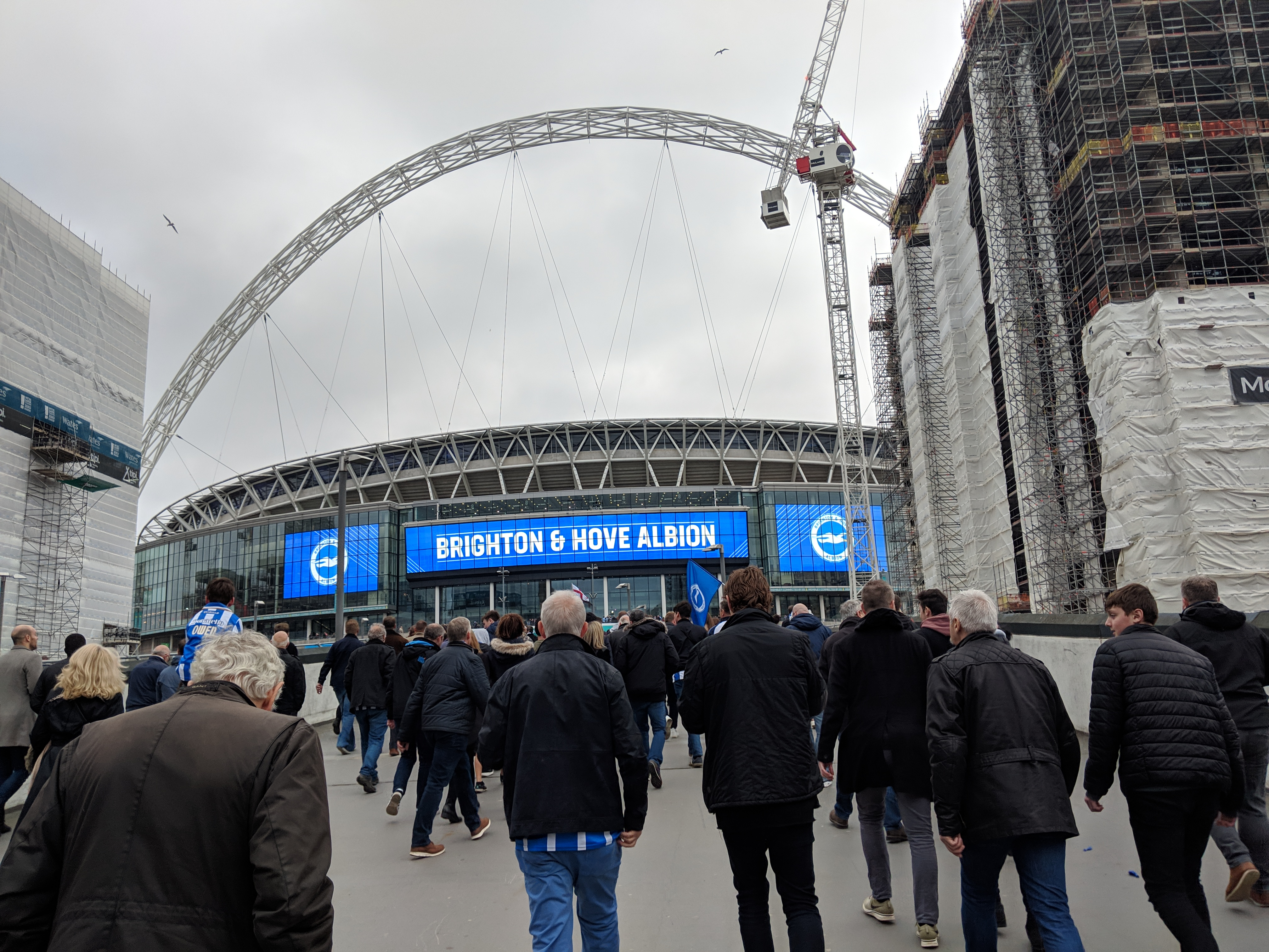 Group of people walking towards Wembley Stadium (London) with a Brighton and Hove Albion banner shown on the outside of the stadium.