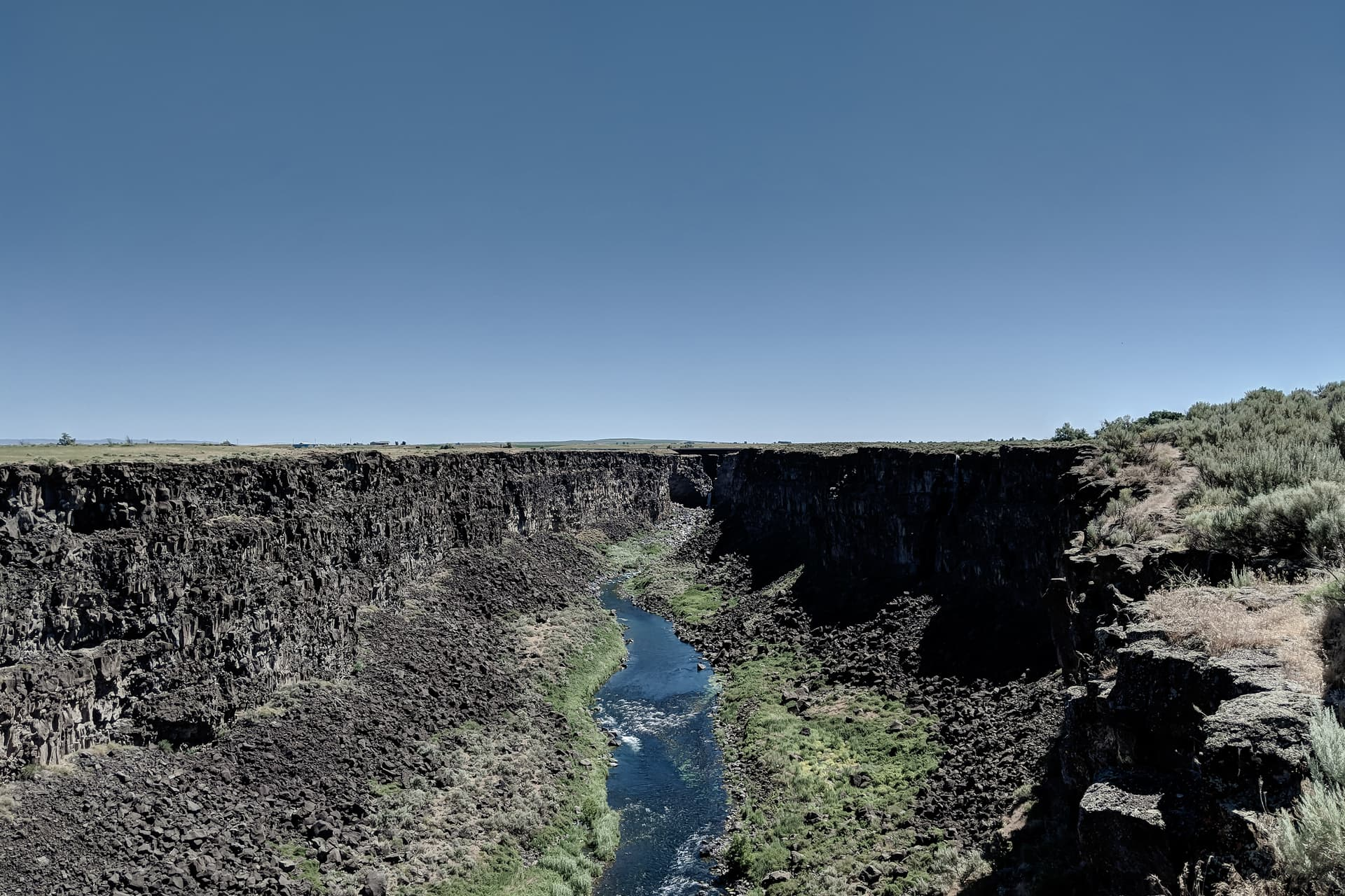 A river cuts a deep, sheer canyon through the basalt underlying otherwise empty desert scrubland. The canyon rim on the right is densely covered in sage, but the left rim is empty.