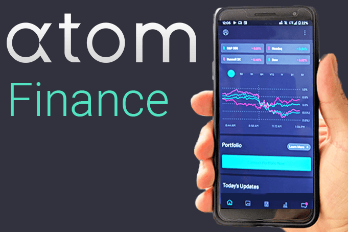 A hand holding a phone showing the Atom Finance app