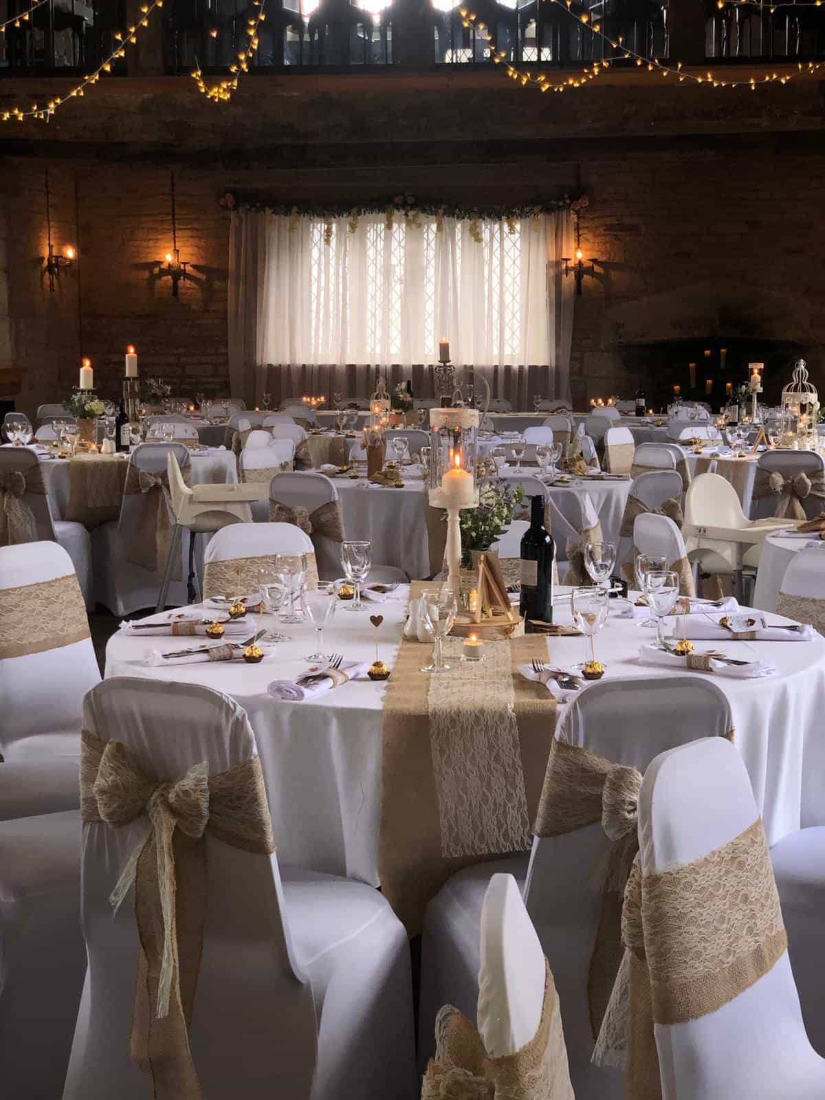 Wedding breakfast venue dressing with white linen and white chairs, and golden highlights throughout room