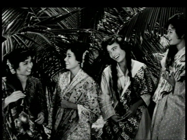 Film still from Tun Fatimah. Four women are smiling at each other.