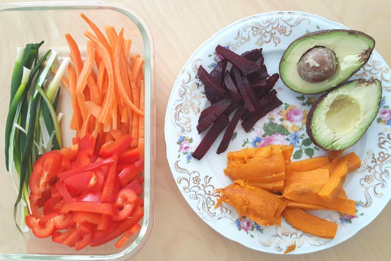 Links eine Schale mit Streifen von Frühlingszwiebeln, Paprika und Möhren, rechts ein Teller mit Rotebeete, Süßkartoffel und einer aufgeschnittenen Avocado.