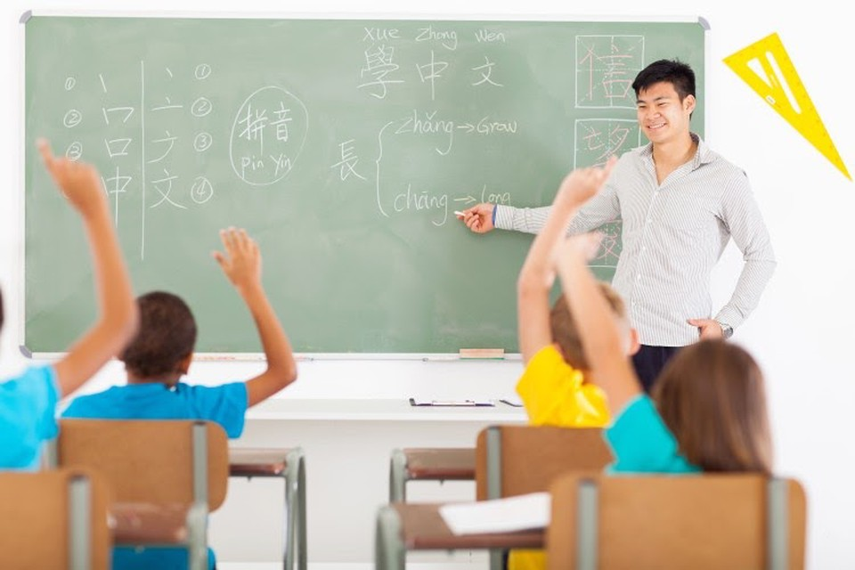 A teacher points to a chalkboard in front of a group of students.