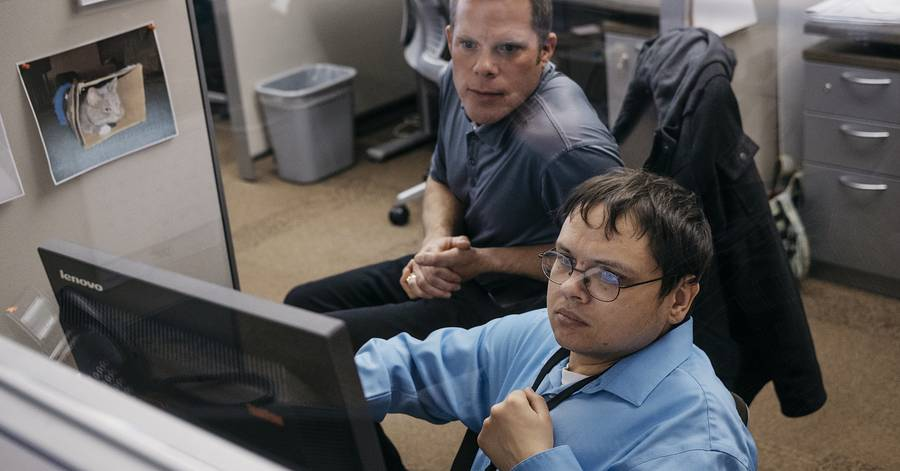 Employee with disability working on computer while supervisor looks on