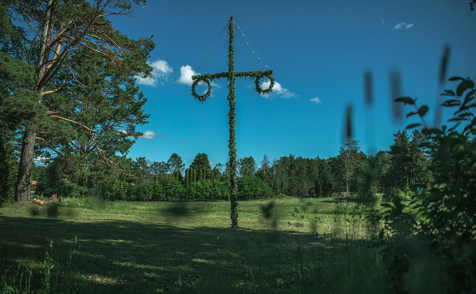 midsommar pole in a green field in sweden