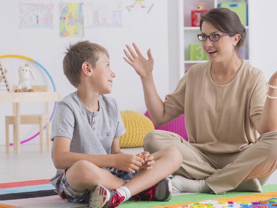 A boy seated at the floor looking at a woman, who is also seated on the floor and has her hands up while talk to the boy