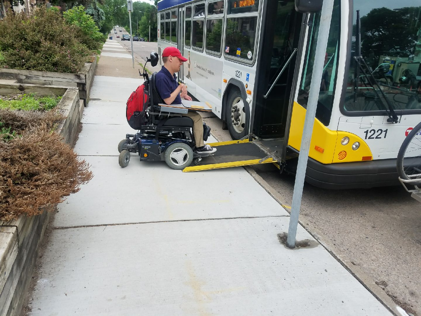 Sam Graves driving wheelchair on to city bus wheelchair ramp