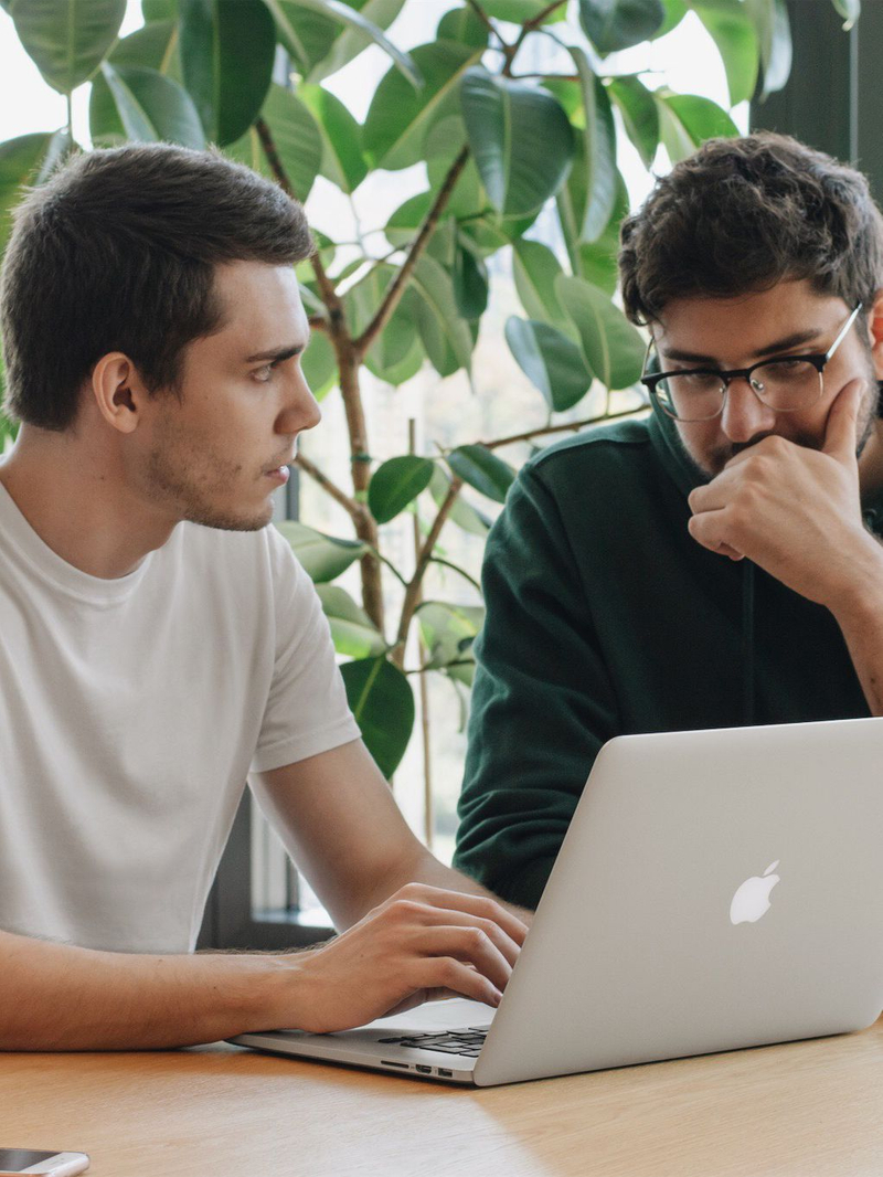 A photo that represents two men talking about something in front of computer