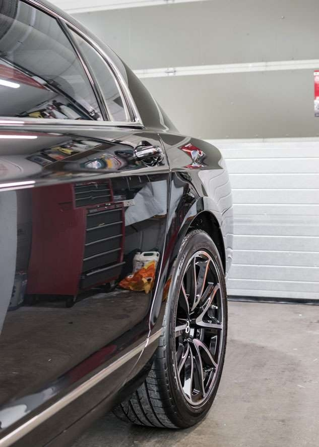 Rear side shot of Bentley Flying Spur car with paintwork shine/gloss restored by polishing, paint correction and paint enhancement