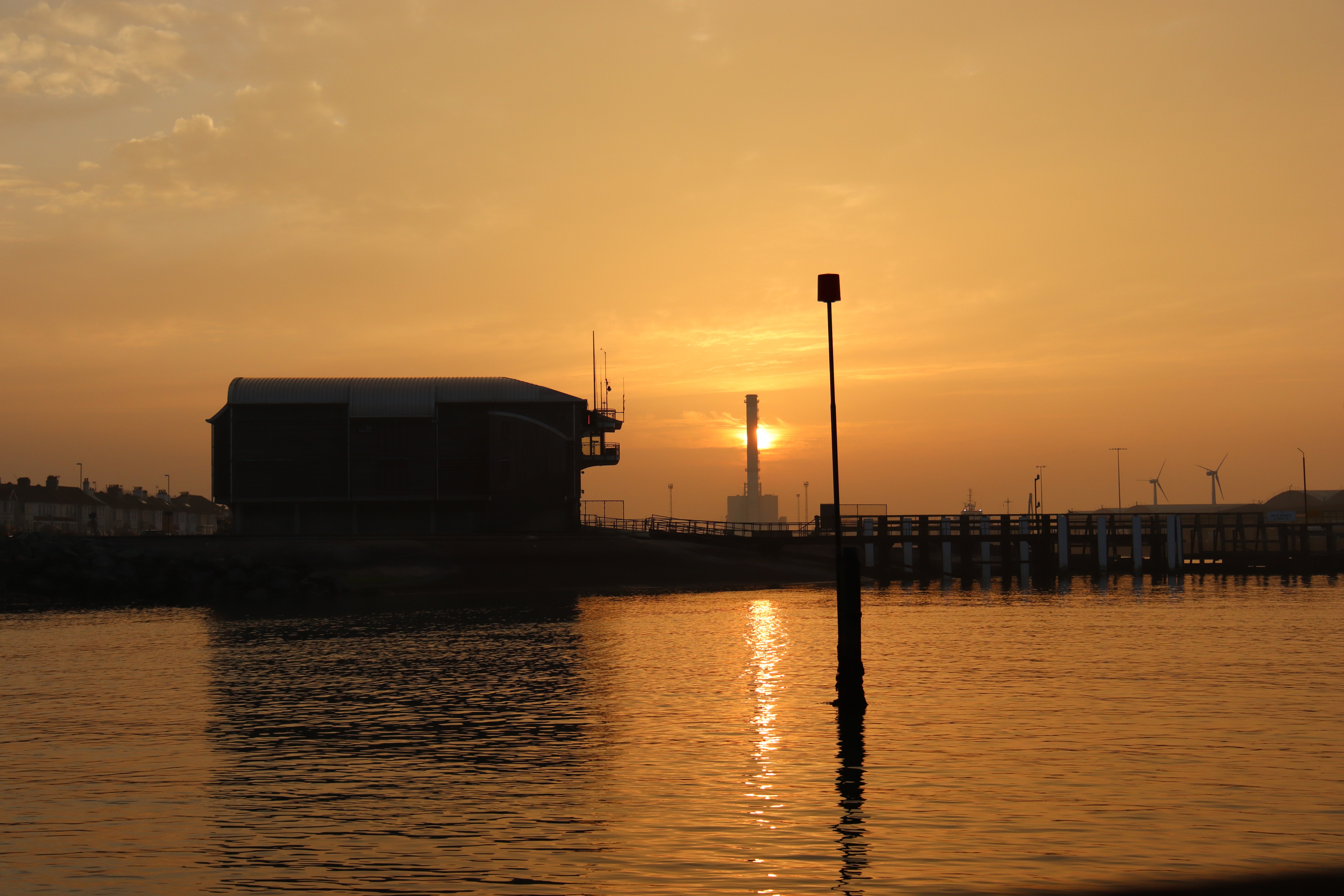 Sun rising behind Shoreham power station and Shoreham lifeboat station. The sunrise is reflecting off the sea below.