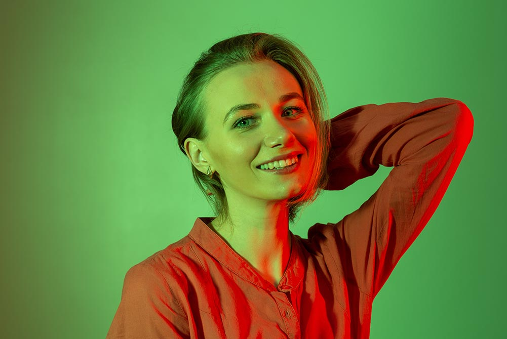 Lady look at camera with tilted head on green background