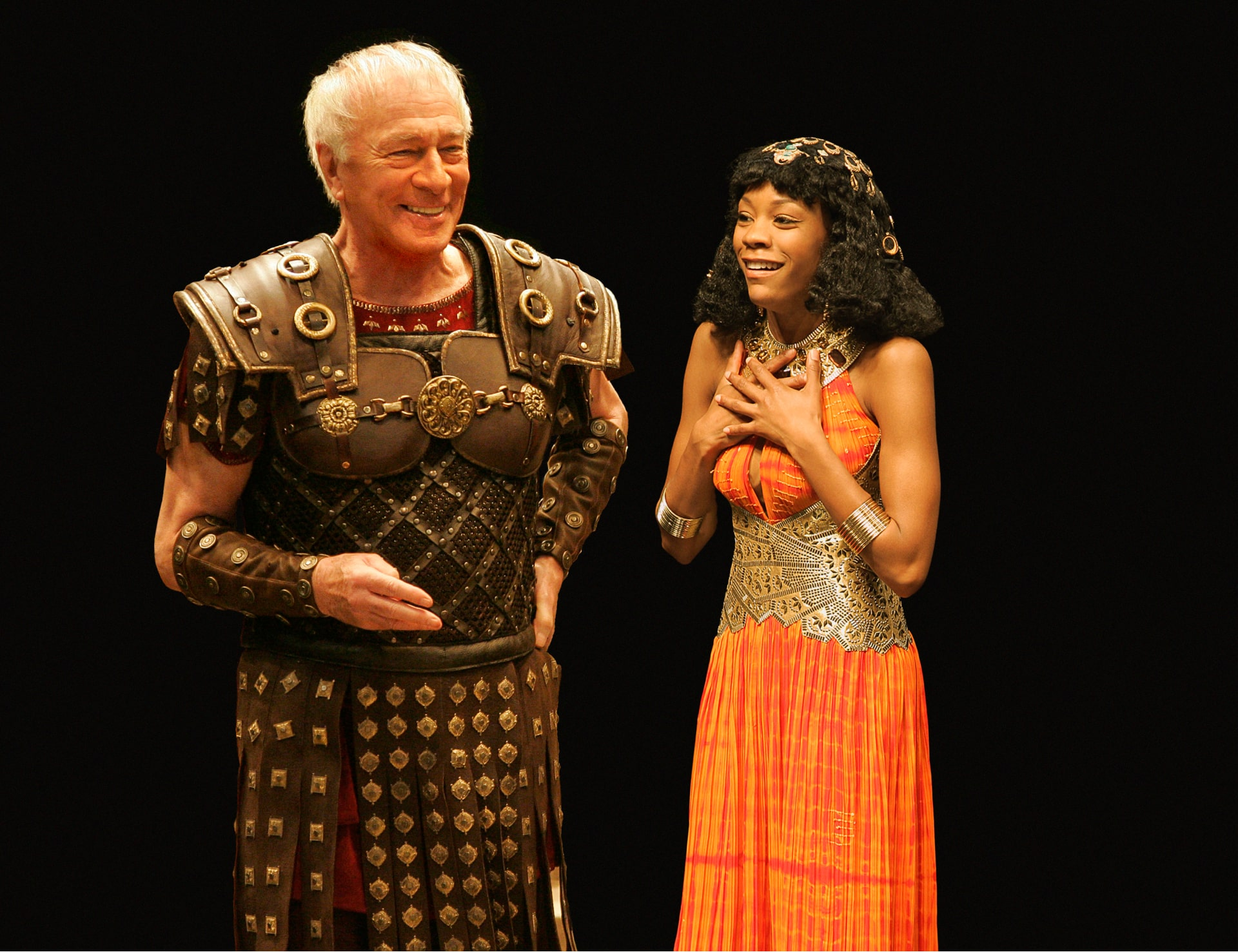 Roman leader and Egyptian queen laugh in warm light.