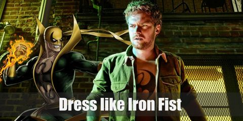 Danny Rand wears a T-shirt with the Iron Fist symbol on it, an opened military green jacket, brown cargo pants, a yellow belt, a yellow mask, yellow finger-less gloves, and brown combat boots.