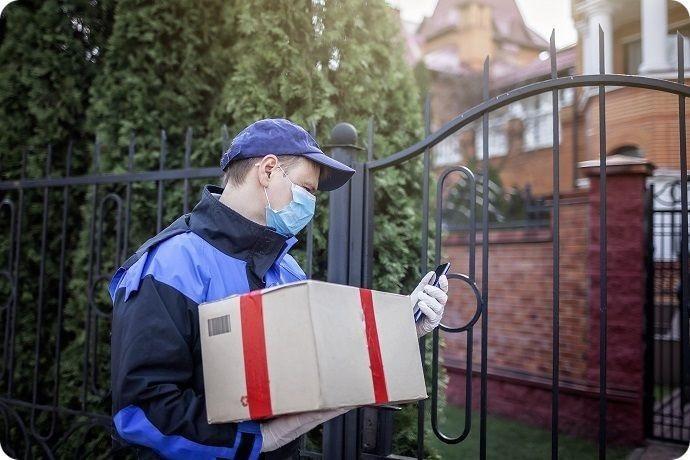 livraison à domicile d'un colis par un personne protégée masque et gants