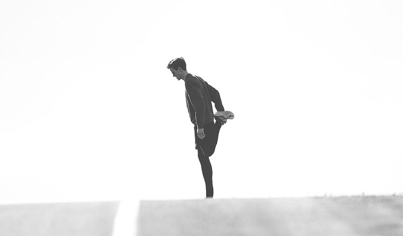 Black and white picture of a man stretching during a run