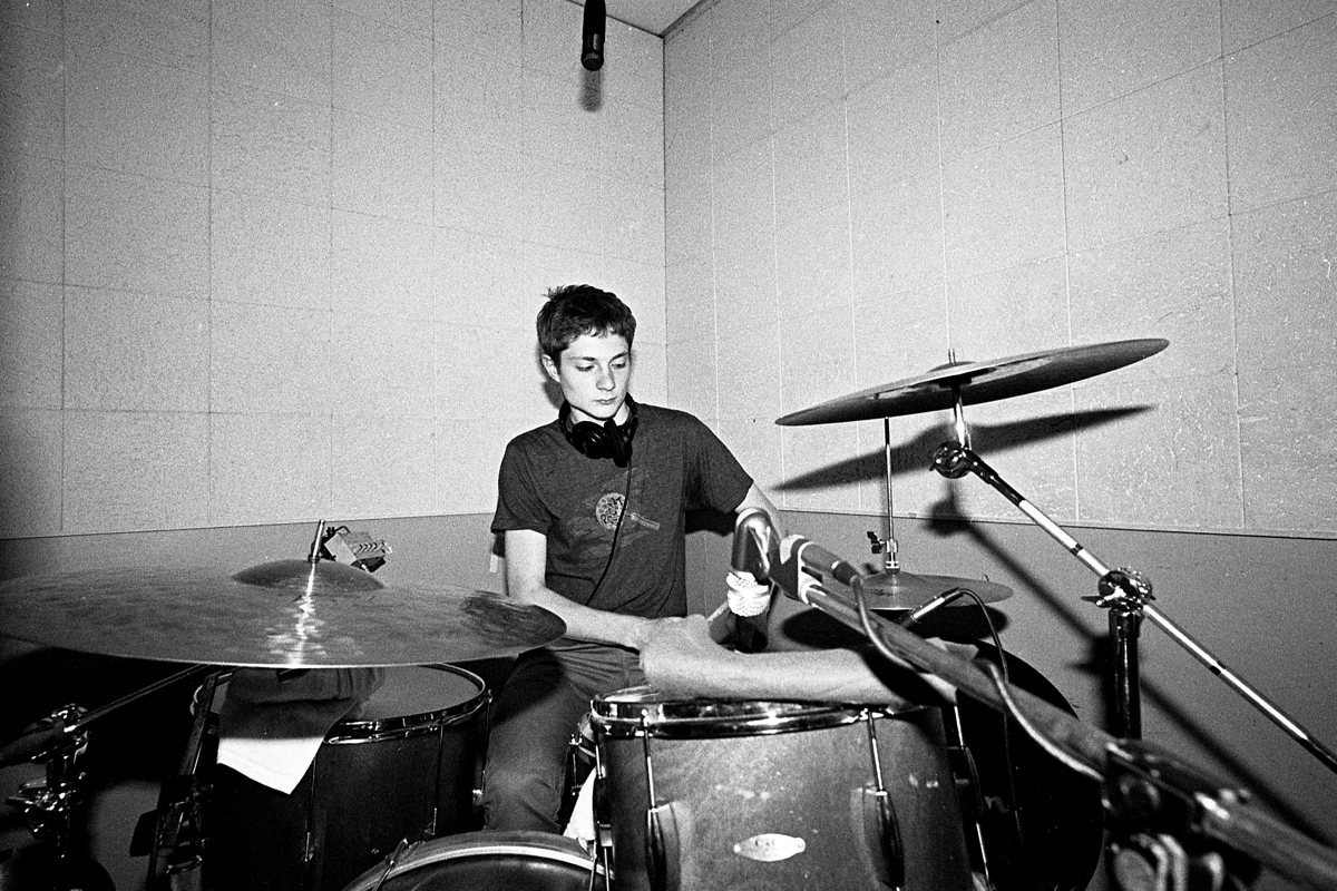 A portrait of Spencer Tweedy playing drums by David Zoubek.