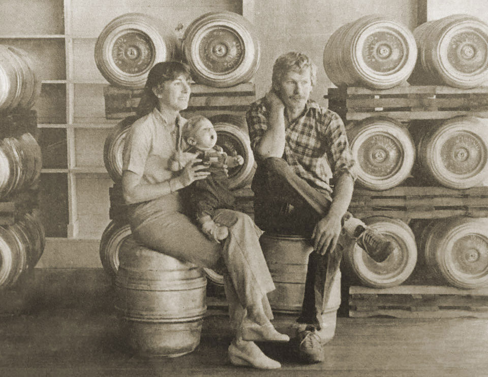 Sepia toned photo of Tom Baune and Beth Hartwell sitting on kegs with kegs stacked up in the background. Beth is holding a baby.