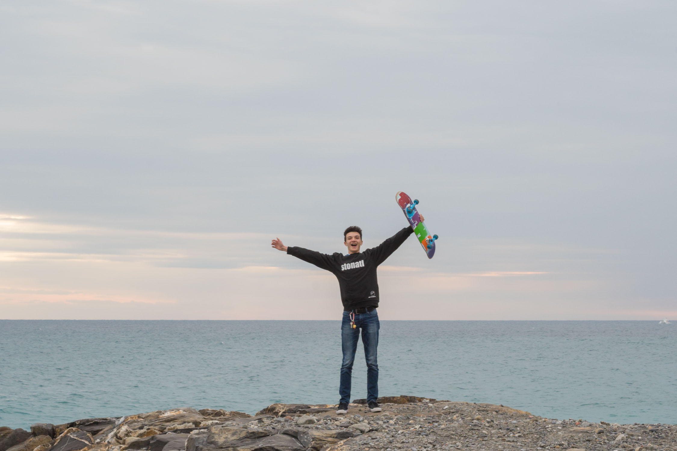 io in piedi su un molo con il mio skateboard in mano