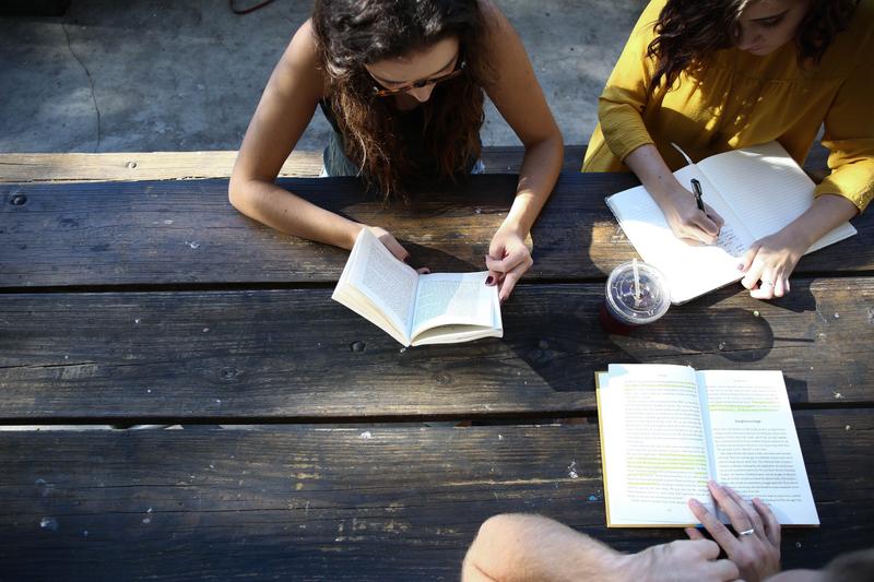 Three students study outside at a picnic bench