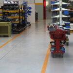 Carrelli, macchine e scaffali organizzati secondo la segnaletica orizzontale integrata nella resina su cui poggiano.