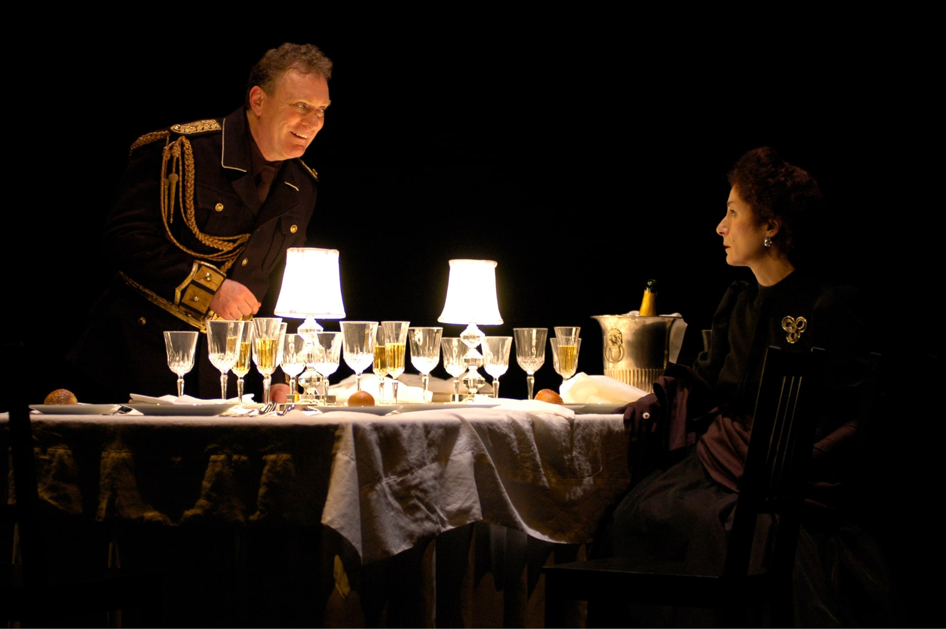 Liveried man leans on table across from seated woman, many crystal goblets between them lit by two small table lamps.