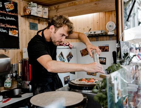 Frische Galette-Zubereitung mit Tomate Mozzarella in gemütlichem Holz-Crepestand