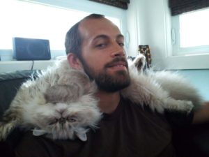 man with a cat on his neck as a pillow