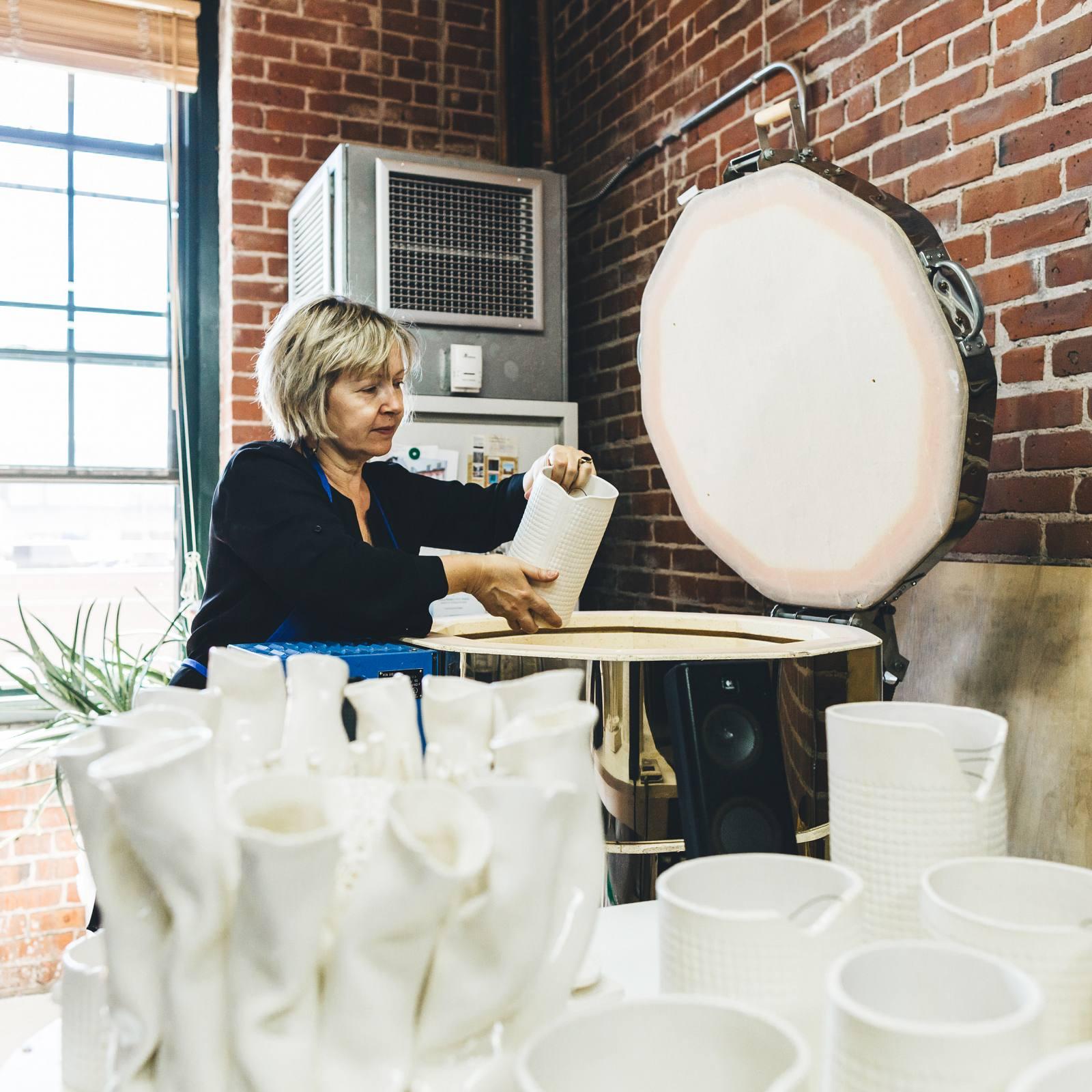 Liliana loading her kiln with ceramic pieces.