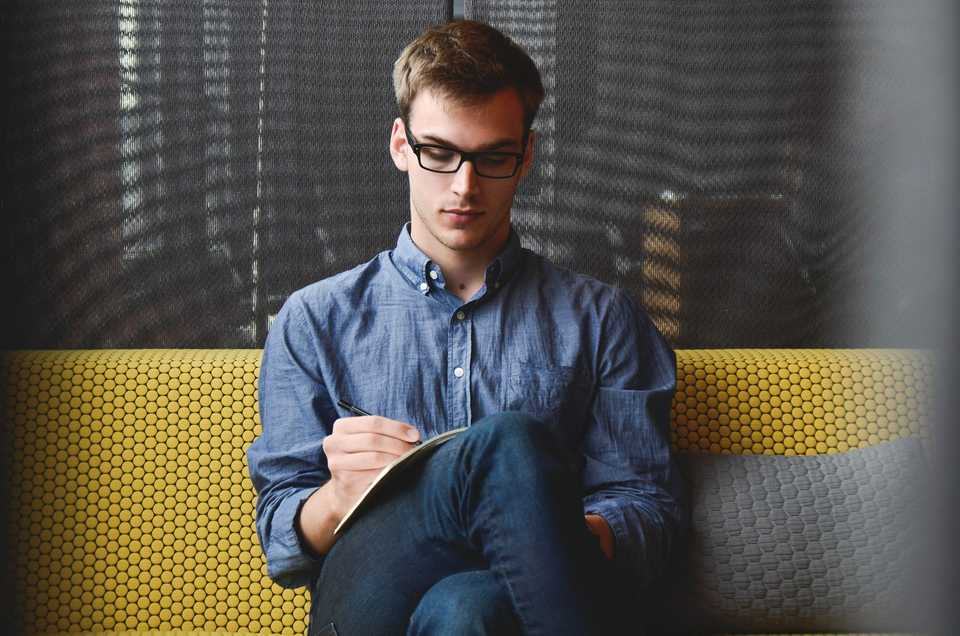Man sits on sofa doing business and writing in his notepad