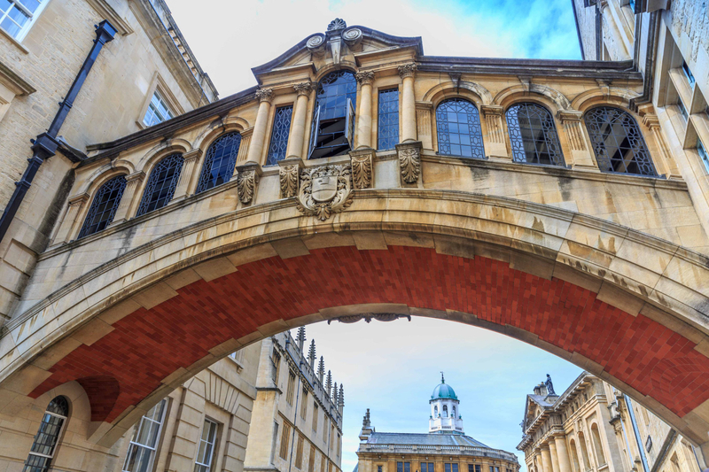An arched walkway with windows connecting two buildings on the Oxford University campus