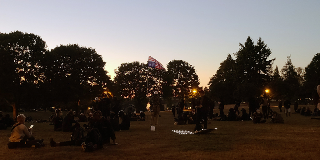 Now, in the light of a fading sun with an American flag flying upside down to display the assembled crowds' distress, new activists and veteran protesters listen to a tiny woman wearing a facemask and tactical body armor. Photo by James O'Ryan.