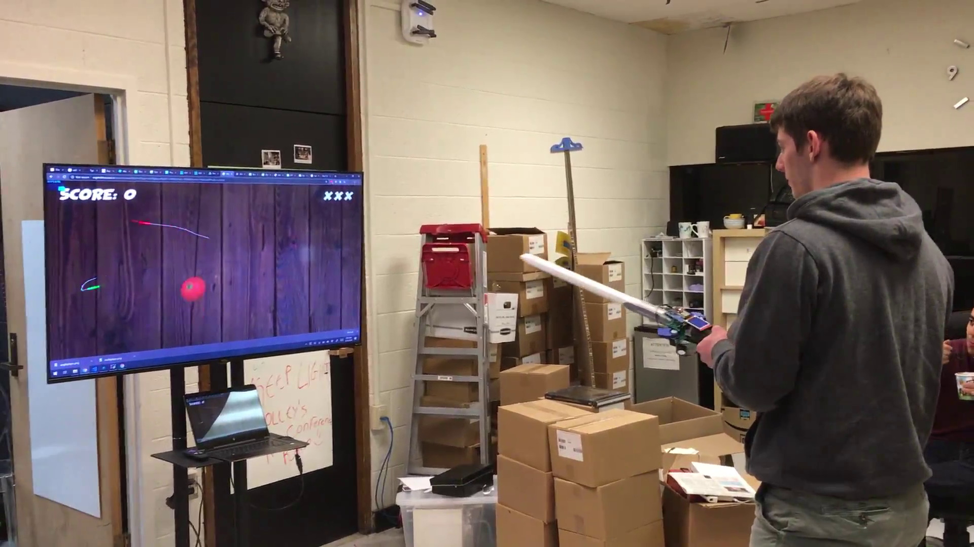 A team member playing vegetable assassin on a large TV
