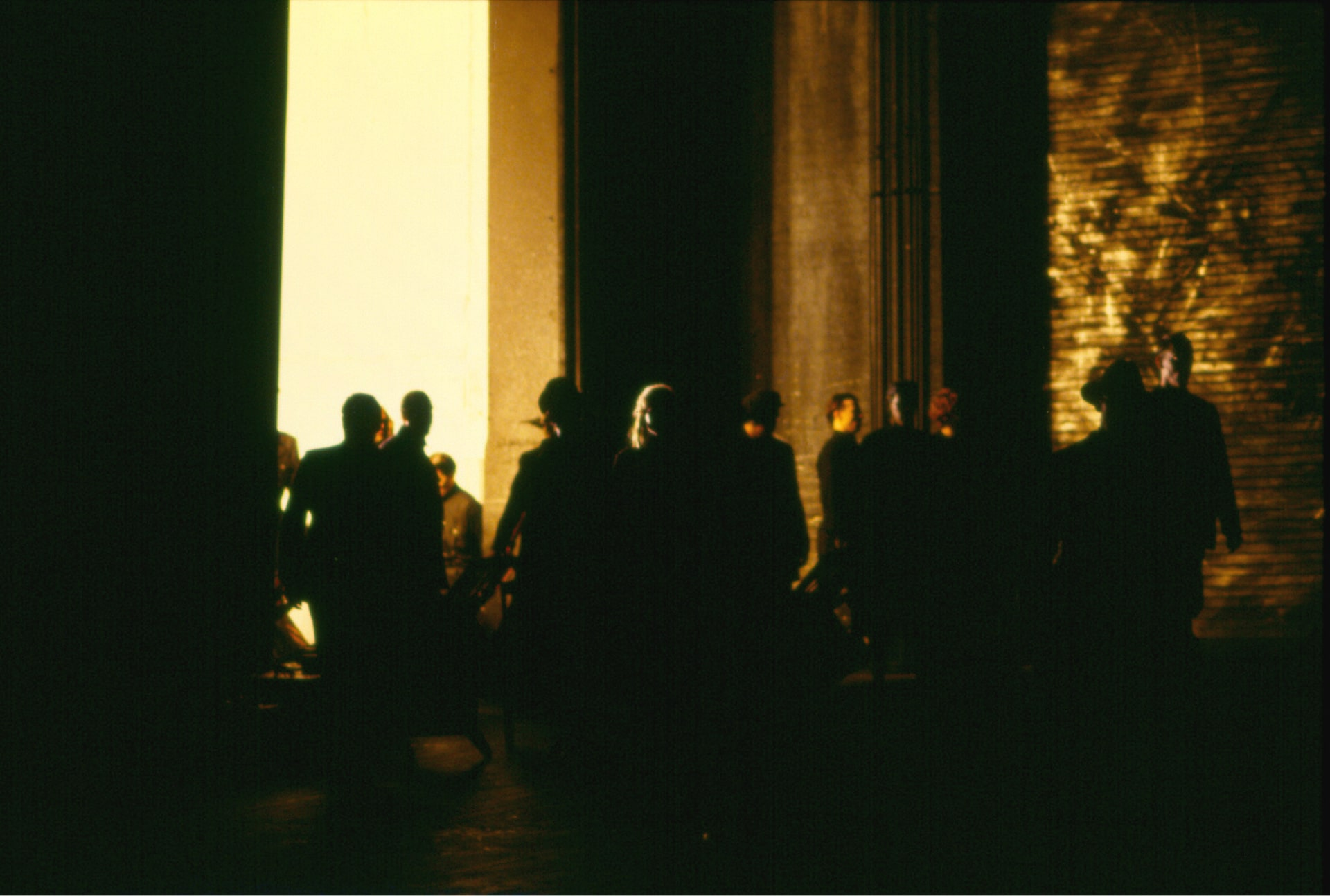 Crowd scattered on darkened stage lit by blinding light through tall open doorway.