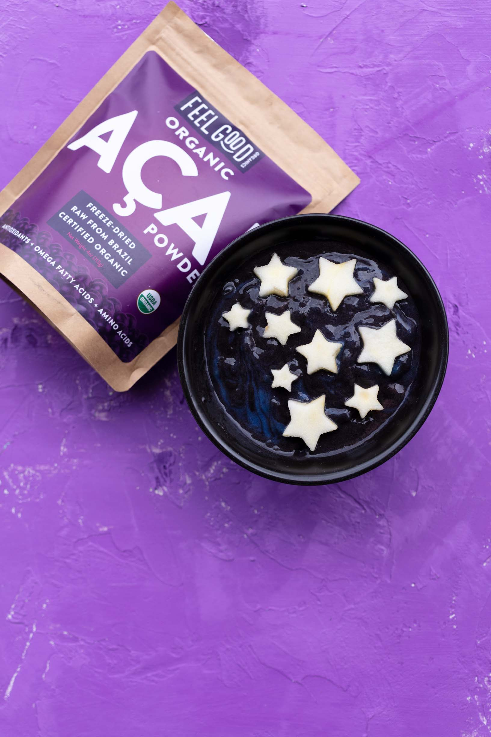 Feel Good Organics acai berry powder next to a galaxy acai smoothie bowl