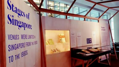 A photo of an exhibition section, titled Stages of Singapore. On the left, there is a table showcase next to a wall.