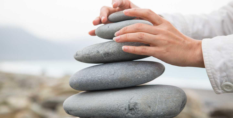 Frauenhände, die Steine aufeinander stapeln - Zinseszinseffekt - So nutzt du ihn für deine Altersvorsorge