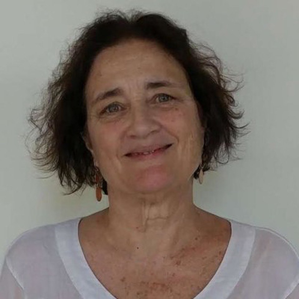 Professor Stephanie Baus - smiling and wearing a white shirt
