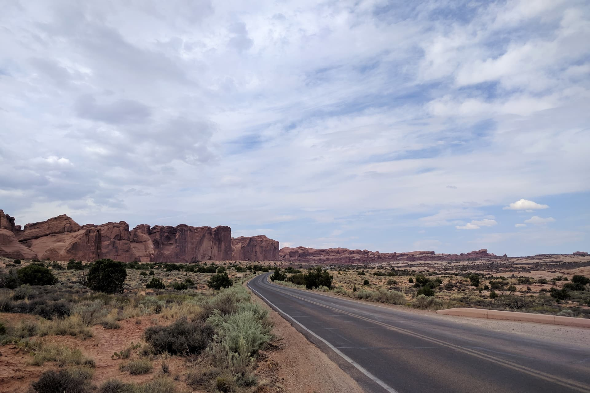 Looking north along the main road into Arches National Park. To the road's left, the undulating wall of a mesa made of red sandstone stretches into the distance.