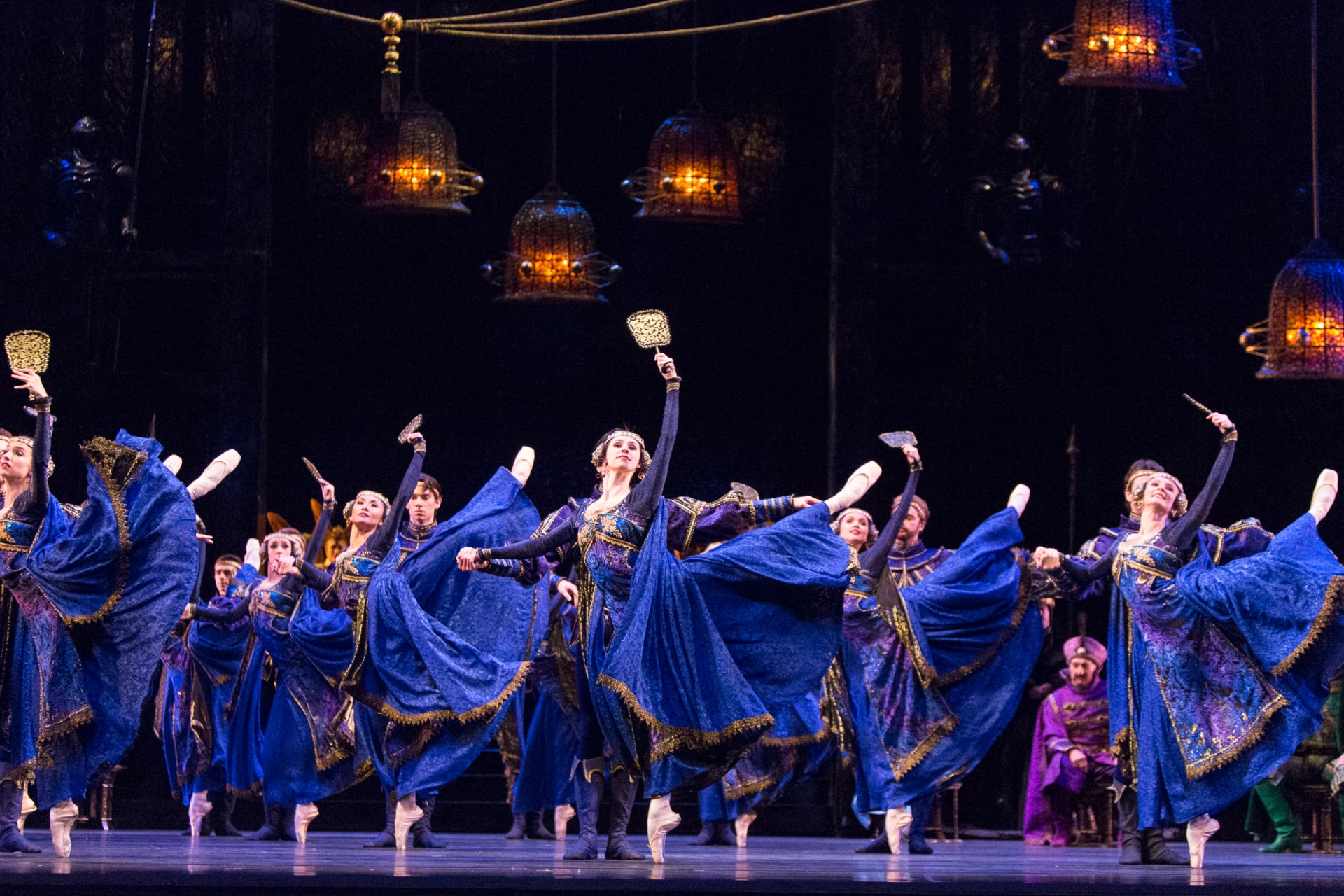 Ballerinas in blue dresses raise hand mirrors on point under amber glass hanging lamps.